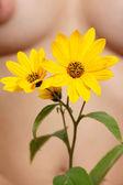 κίτρινο λουλούδι κατά ένα γυναικείο σώμα — Φωτογραφία Αρχείου
