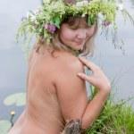 Girl posing topless against river — Stock Photo